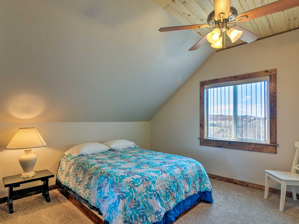 The first bedroom at Sunrise Hollow features a comfy queen bed, ceiling fan, knotty aspen lined ceiling, and panoramic views of red rock country in the distance.