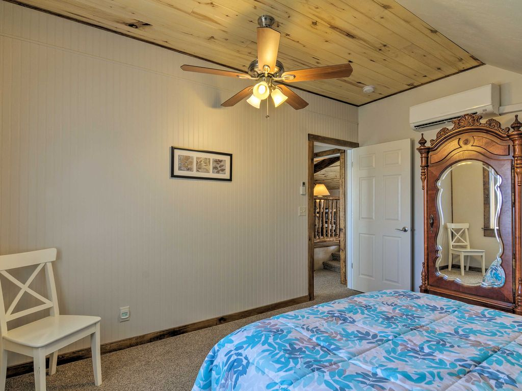 Sunrise Hollow's first bedroom features an elegant wardrobe, comfy queen bed, private climate control, and panoramic views of Bryce Canyon in the distance.