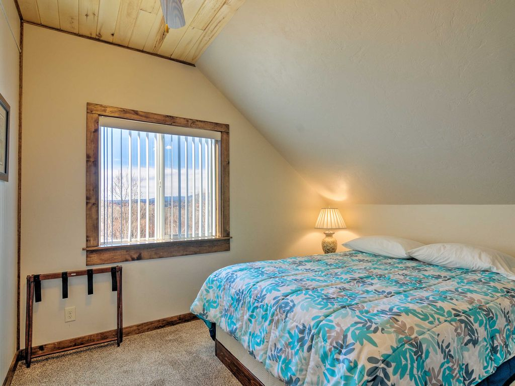 The second bedroom at Sunrise Hollow features a comfy queen bed, knotty aspen lined ceiling, and a ceiling fan, plus a panoramic view of the rim of Bryce Canyon in the distance.