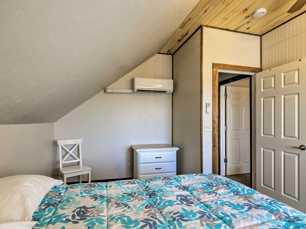 The second bedroom at Sunrise Hollow feature a comfy queen bed, knotty aspen lined ceiling, a ceiling fan, and private climate control.
