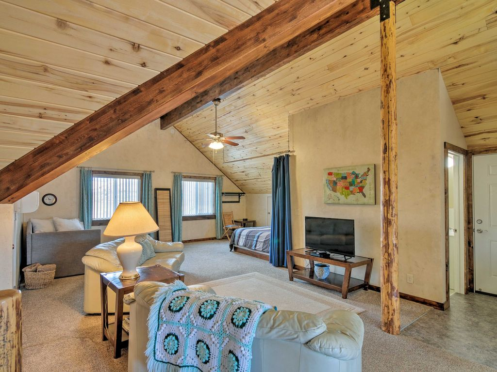 The spacious great room at Sunrise Hollow features leather couches, a flatscreen TV, and a sleeping nook with an extra queen bed! Notice the rustic cedar post and aspen-lined ceiling.